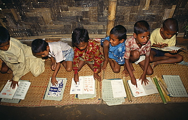 Schoolboys sitting on mats on floor of village school learning to read, Bangladesh, Asia