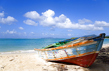 Waves breaking on Paradise Beach at LEsterre Bay with an old fishing boat on the shore and the turqoise sea and Sandy Island sand bar beyond, Grenada