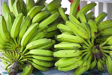 Hillsborough Bundles of green bananas on a stall in the main street, Caribbean