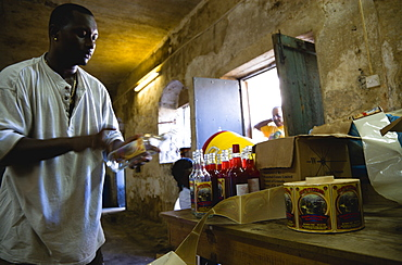 Male worker hand labelling the bottles at the River Antoine rum distillery, Caribbean
