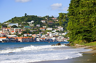 The hillside buildings and waterfront of the Carenage in the capital St Georges seen from Pandy Beach beside Port Louis Marina, Caribbean
