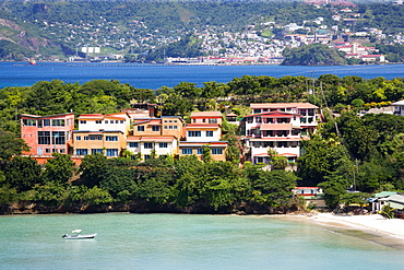 BBC Beach in Morne Rouge Bay lined with holiday apartment villas and the capital of St Georges in the distance, Caribbean