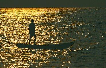 TANZANIA  Lake Tanganyika  Mokoro canoe raft paddler on lake at sunset
