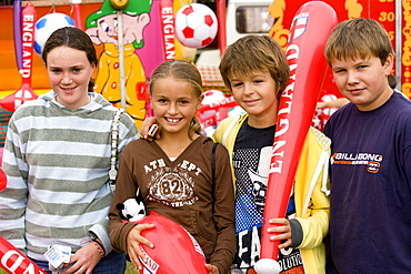 Findon village Sheep Fair Two teenage boys and two girls holding prizes won at fairground stalls, United Kingdom