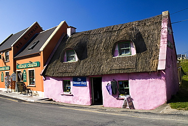 Ireland, Couty, Clare, Doolin, Colourful craft shops in village - one with thatched roof