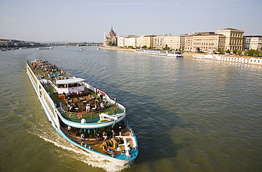 Hungary, Pest County, Budapest, pleasure cruise boat on the River Danube approaching Szechenyi Chain Bridge or Memory Bridge with Hungarian Parliament Building behind on right on Pest bank