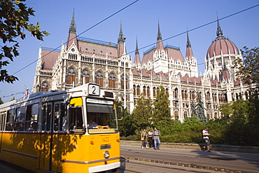 Hungary, Pest County, Budapest, yellow tram passing the Neo-Gothic exterior facade of the Parliament Building with pedestrians on pavement beyond tram line