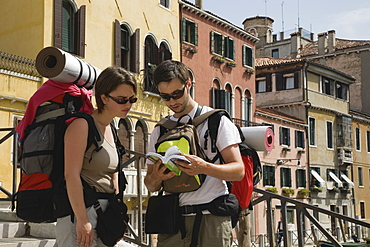 Italy, Veneto, Venice, Two young backpacker tourists wearing sunglasses and carrying rucksacks, rolled up sleeping mats and moneybelts, consulting guide book while standing on canal bridge in Centro Storico centre of Venice
