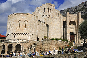Albania, Kruja,  Kruja Castle and Skanderbeg Museum exterior with tourist visitors and souvenir stalls in foreground.