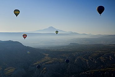 Turkey, Cappadocia, Goreme, Early morning with hot air balloons in flight mist drifting across landscape and Mount Erciyes in the background.