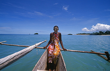 MADAGASCAR  Nosy Be Young girl on a pirogue canoe wearing a colourful sarong and with her face painted.  Turquoise sea.