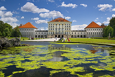 Germany, Bavaria, Munich, Nymphenburg Palace. Baroque exterior facade set in formal gardens with lake in foreground.