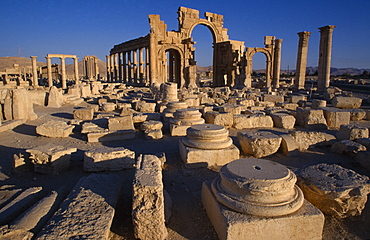 SYRIA Central Tadmur Monumental arch.  High central arch flanked by a lower arch on each side with colonnaded street part seen  behind and masonry ruins in the foreground. Palmyra  Palmyra