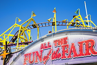 England, Lincolnshire, Skegness, Facade of amusement arcade with rollercoaster behind in clear blue sky.