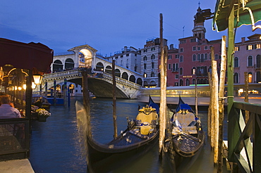 Gondolas moored on the Grand Canal at Riva del Vin, with Rialto bridge behind, Venice, UNESCO World Heritage Site, Veneto, Italy, Europe