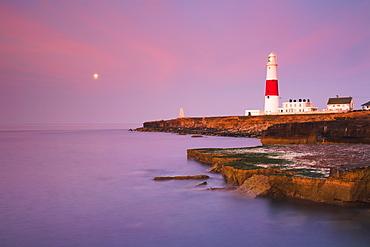 A full moon in the dawn sky over Portland Bill lighthouse, Jurassic Coast, UNESCO World Heritage Site, Dorset, England, United Kingdom, Europe