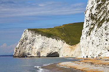 Holidaymakers wander along the beach at Durdle Door, towards Bats Head Cliff, Dorset, England, United Kingdom, Europe