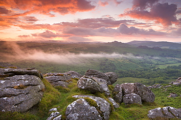 Dramatic sunset above a misty moorland near Hound Tor, Dartmoor National Park, Devon, England, United Kingdom, Europe