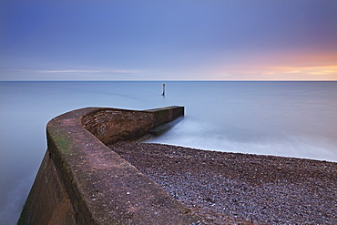 Stone jetty on Sidmouth beachfront at sunset, Sidmouth, Devon, England, United Kingdom, Europe