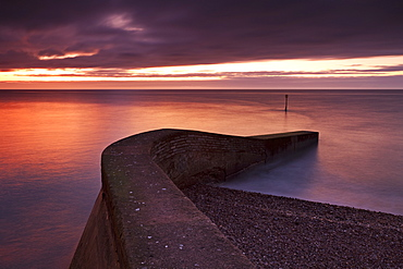 Stone jetty on Sidmouth beachfront at sunrise, Sidmouth, Devon, England, United Kingdom, Europe