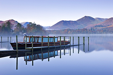 Pleasure boat moored on a placid Derwent Water on a misty and frosty morning, Keswick, Lake District, Cumbria, England, United Kingdom, Europe