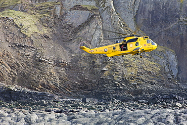 RAF helicopter performing a coastal rescue at the base of the steep cliffs of Spekes Mill Mouth, Hartland, Devon, England, United Kingdom, Europe