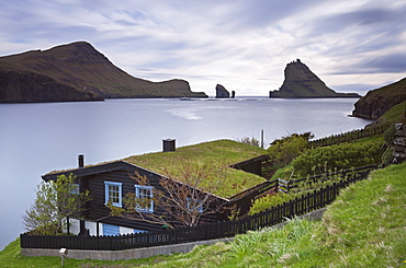 Traditional grass roofed house in the village of Bour, with views to Tindholmur, Vagar, Faroe Islands, Denmark, Europe