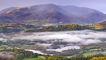 Autumn mist hangs above Elterwater with views beyond to Little Langdale and Wetherlam, Lake District National Park, Cumbria, England, United Kingdom, Europe