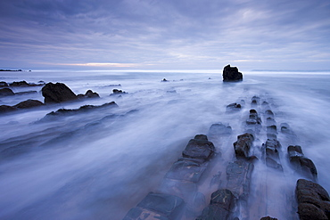 Waves rush over the rocky ledges at Sandymouth Bay in North Cornwall, England, United Kingdom, Europe