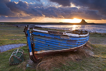 Decaying fishing boat on Holy Island at dawn, with Lindisfarne Castle beyond, Northumberland, England, United Kingdom, Europe