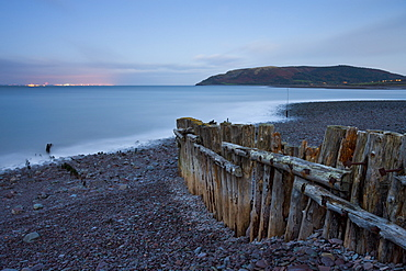 Weathered coastal defences at Porlock Weir in Exmoor National Park, with the evening lights of Wales visible across the Bristol Channel, Somerset, England, United Kingdom, Europe