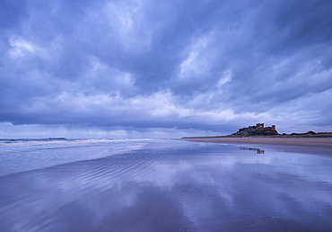 Storm clouds reflect on the deserted beach beside Bamburgh Castle in winter, Northumberland, England, United Kingdom, Europe