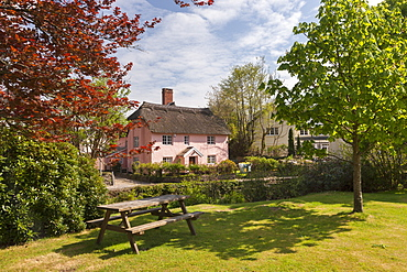 Picnic bench and pretty pink cottage in the village of Winsford, Exmoor National Park, Somerset, England, United Kingdom, Europe