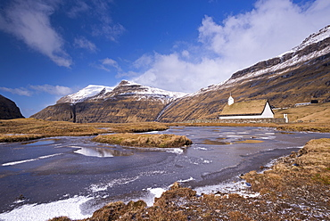 Spectacular mountain scenery surrounding Saksun and pretty turf roofed church, Streymoy, Faroe Islands, Denmark, Europe