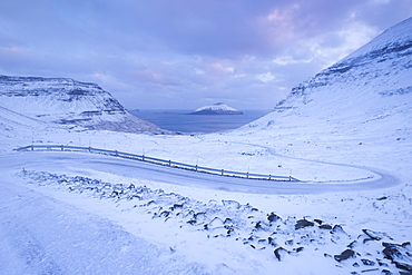Snow covered road winding down between mountains near Nordradalur on the Island of Streymoy, Faroe Islands, Denmark, Europe