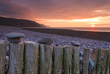Pebbles on wooden posts at sunset, Bossington Beach, Exmoor National Park, Somerset, England, United Kingdom, Europe