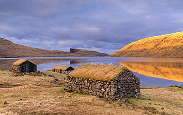 Grassed roof stone barns on the shores of Sorvagsvatn (Leitisvatn Lake) on the island of Vagar in the Faroe Islands, Denmark, Europe