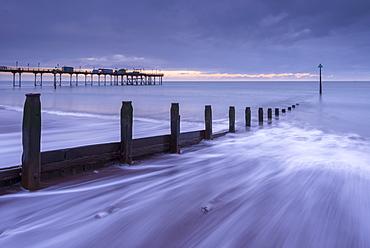 Waves wash against the wooden groynes near Teignmouth Pier at sunrise, Devon, England, United Kingdom, Europe