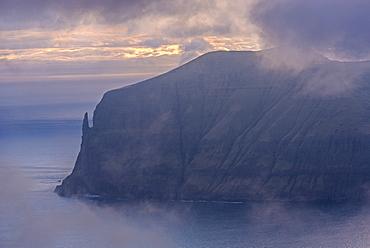 Sunset behind the Trollkonufingur (Troll Finger) and the immense sea cliffs of the island of Vagar, Faroe Islands, Denmark, Europe