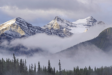 Early morning mist hangs in the wooded valleys below the snow capped mountains of the Canadian Rockies, Banff, Alberta, Canada, North America