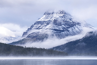 Snow dusted Bow Peak mountain surrounded by mist, viewed from across Bow Lake, Icefields Parkway, Alberta, Canada, North America