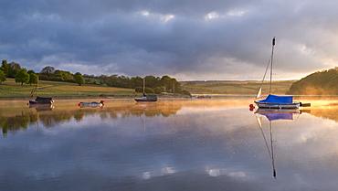 Boats on a reflective Wimbleball Reservoir at sunrise, Exmoor National Park, Somerset, England, United Kingdom, Europe