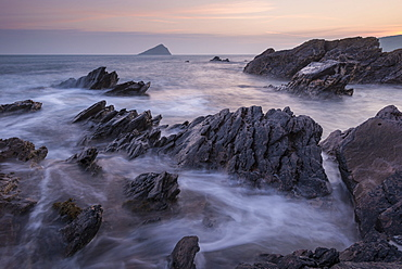 Pastel sunset sky over the Great Mewstone from the rocky shores of Wembury Bay, Devon, England, United Kingdom, Europe