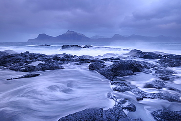 Waves wash over the dark basalt ledges of Gjogv on a stormy evening in the Faroe Islands, Denmark, Europe