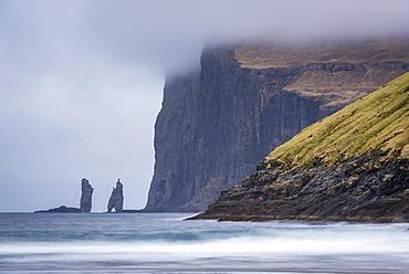 The sea stacks Risin og kellingin at the base of dramatic cliffs on Eysturoy in the Faroe Islands, Denmark, Europe