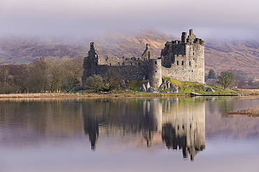 The ancient ruins of Kilchurn Castle, reflected in Loch Awe in winter, Dalmally, Argyll and Bute, Scotland, United Kingdom, Europe