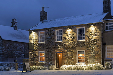 Welcoming village inn on a snowy winter evening, Bamburgh, Northumberland, England, United Kingdom, Europe
