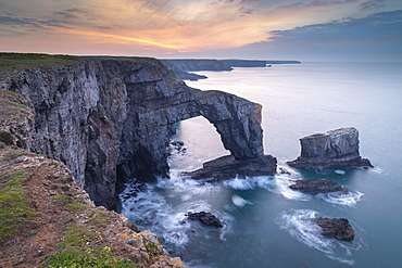 Colourful dawn sky above the Green Bridge of Wales natural arch in Pembrokeshire, Wales, United Kingdom, Europe