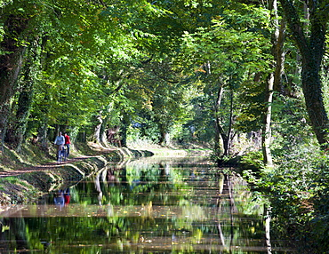Cyclists riding along the tow path beside the Monmouthshire and Brecon Canal at Llangattock, Brecon Beacons National Park, Powys, Wales, United Kingdom, Europe