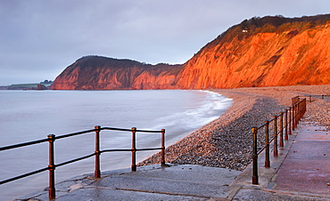Early morning sunlight glows against the distinctive red cliffs of High Peak, viewed from the beach at Sidmouth, Devon, England, United Kingdom, Europe